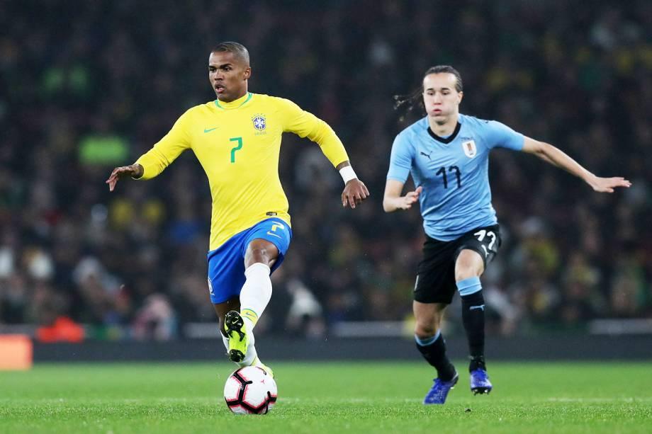 Douglas Costa (esq) disputa bola com Diego Laxalt (dir), durante amistoso entre Brasil e Uruguai, realizado no Emirates Stadium, em Londres - 16/11/2018