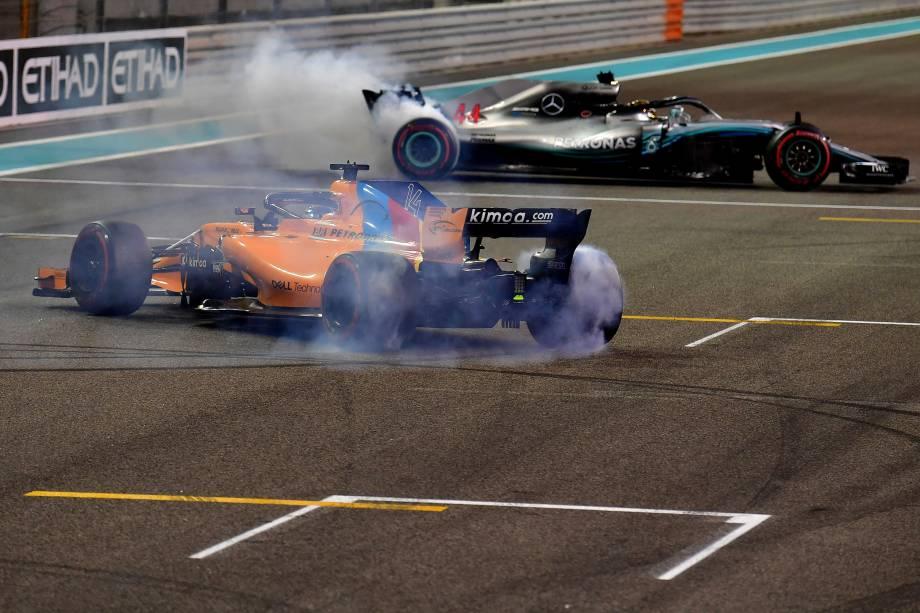 O piloto espanhol da McLaren, Fernando Alonso, acompanha Lewis Hamilton da Mercedes depois de sua última corrida de F1 no Grande Prêmio de Abu Dhabi