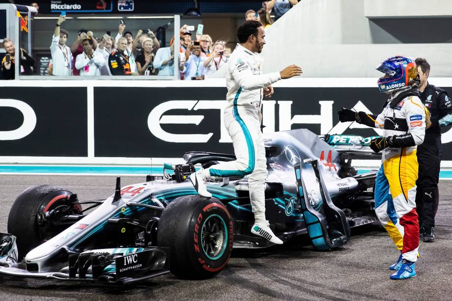 O vencedor da corrida, o britânico Lewis Hamilton da Mercedes comemora com Fernando Alonso da McLaren na despedida do piloto espanhol da F1 após o Grande Prêmio de Abu Dhabi