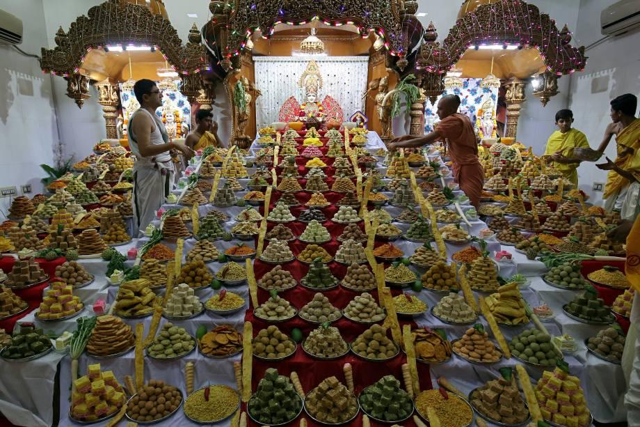 """Sacerdote organiza doces guardados dentro de um templo como oferendas de devotos hindus para um ritual que marca o festival """"Annakut"""" durante o Diwali, o festival hindu das luzes, em Ahmedabad, na Índia - 07/11/2018"""