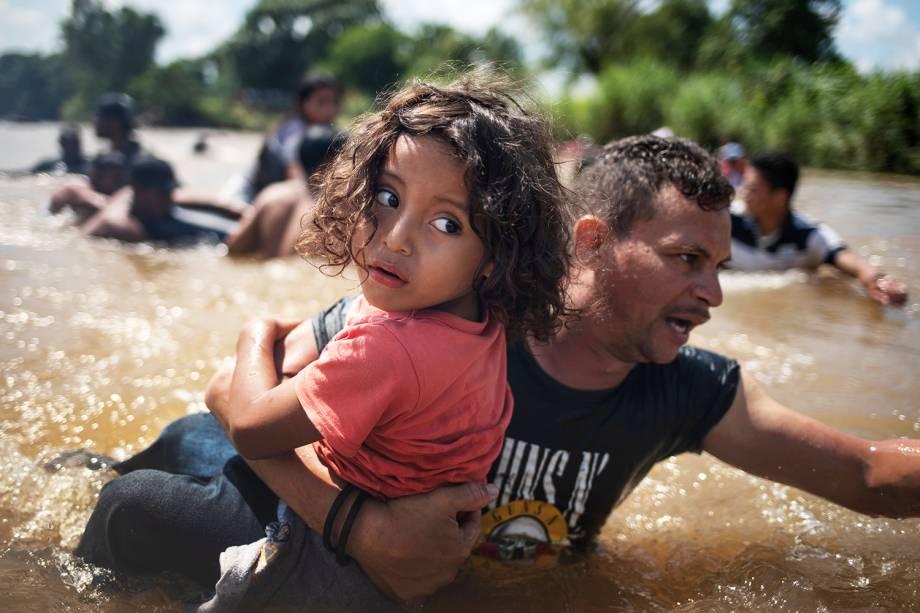Pai carrega filho durante passagem pelo rio Suchiate, localizado na cidade mexicana de Ciudad Hidalgo, durante caravana de imigrantes da América Central, rumo aos Estados Unidos - 29/10/2018