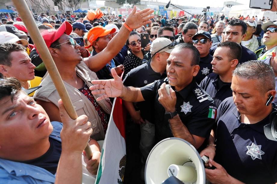 Migrantes negociam com policiais para atravessarem fronteira entre o México e os Estados Unidos, na cidade de Tijuana - 22/11/2018