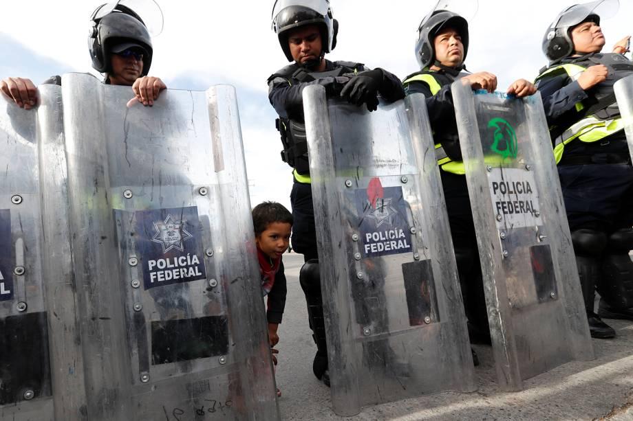 Criança é vista atrás de escudo de policial mexicano, próxima da fronteira entre o México e os Estados Unidos, na cidade de Tijuana - 22/11/2018