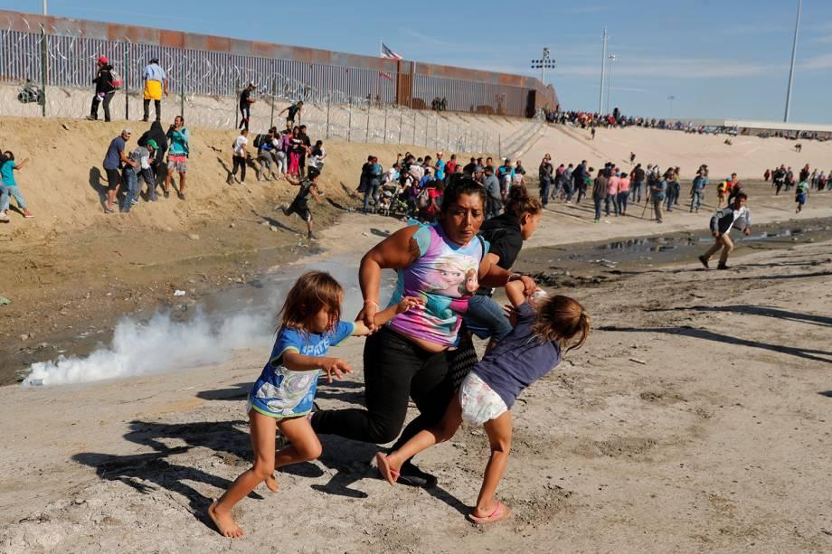 Família de migrantes se dispersam de confronto com policiais, na tentativa de atravessar a fronteira entre o México e os Estados Unidos, na cidade de Tijuana - 25/11/2018