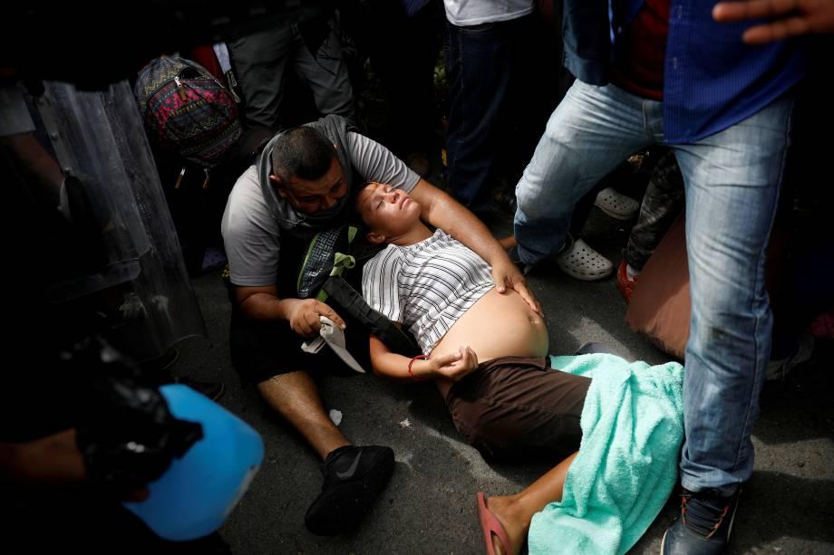 Imigrante grávida, parte da caravana de El Salvador que tenta entrar nos Estados Unidos desmaia durante uma operação da polícia mexicana para detê-los por entrar ilegalmente no país, em Metapa - 21/11/2018