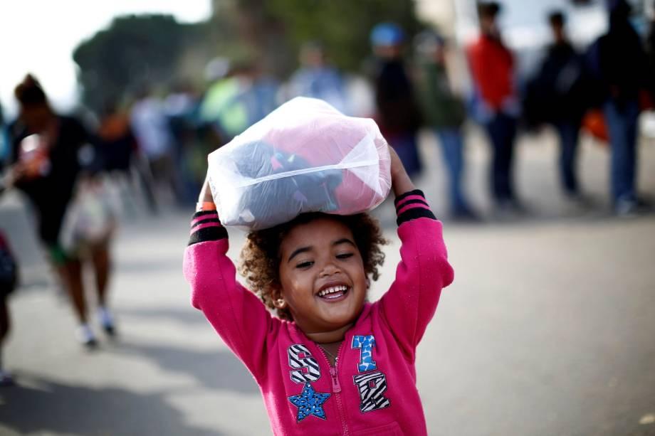 Menina hondurenha, parte da caravana de milhares de pessoas que viajam a caminho dos Estados Unidos, sorri enquanto carrega roupas doadas em um abrigo da cidade mexicana de Tijuana - 21/11/2018