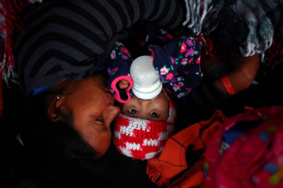 Imigrantes da caravana da América Central que tenta chegar aos Estados Unidos, descansam no porto de El Chaparral fronteira entre México e Estados Unidos, em Tijuana - 23/11/2018