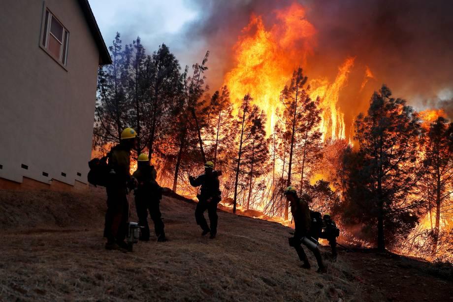 Membros do Serviço Florestal dos EUA trabalham para conter chamas que avançam para cima de uma casa durante o incêndio florestal que atingiu a cidade de Paradise, na Califórnia - 08/11/2018