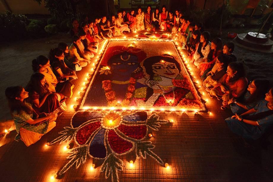 """Meninas indianas acendem lâmpadas de barro em um """"Rangoli"""" como eles celebram Diwali, o Festival das luzes, na cidade de Guwahati - 06/11/2018"""
