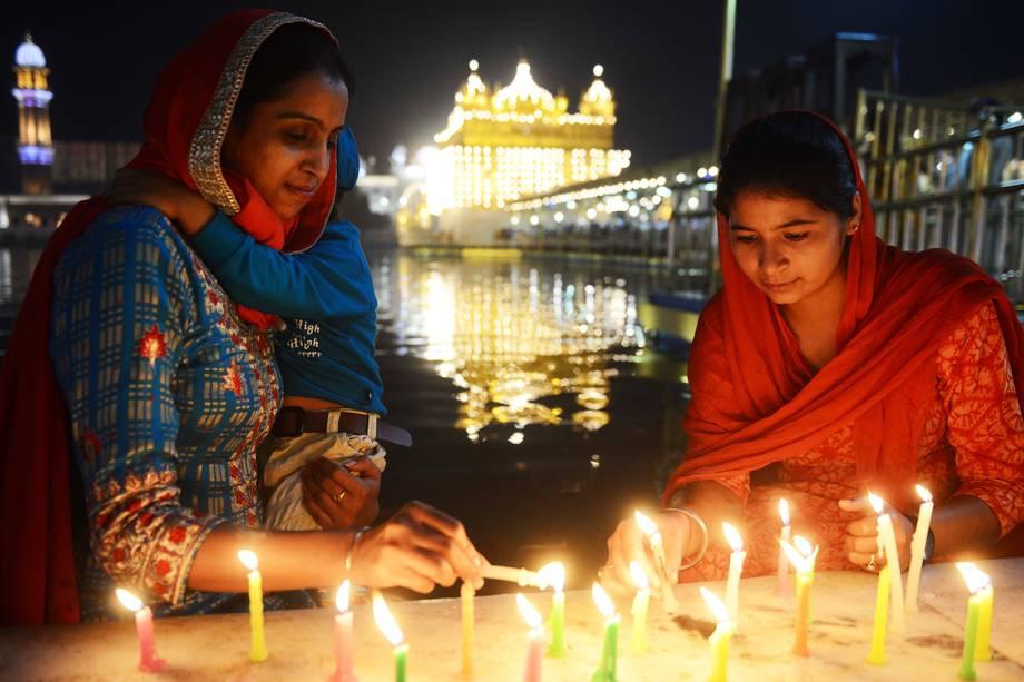 Devotas indianas acendem velas às vésperas do festival Diwali, conhecido como o 'Festival das Luzes',  no Templo Dourado, em Amritsar - 06/11/2018