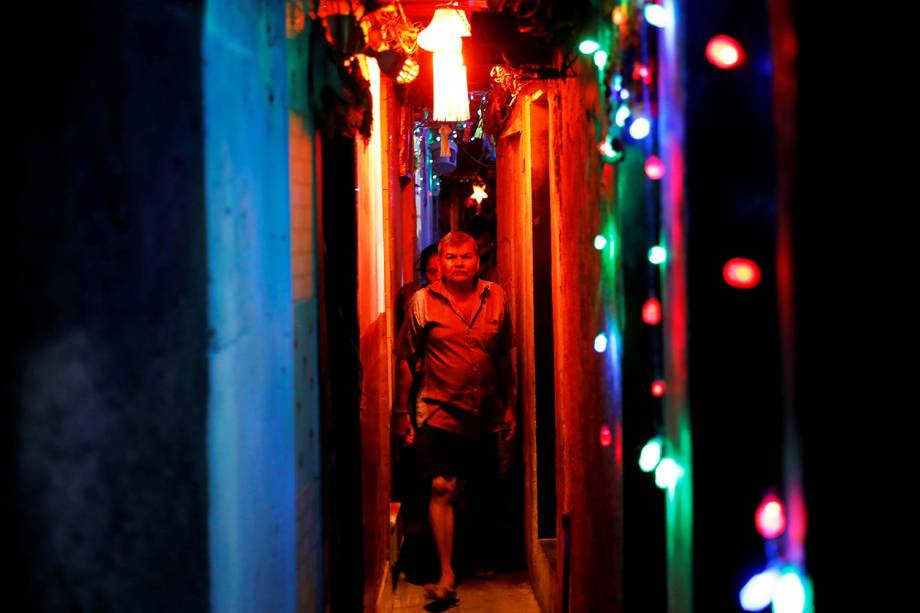 Moradores caminham em beco de uma favela iluminado por luzes coloridas às vésperas do festival hindu Diwali em Mumbai, na Índia - 06/11/2018