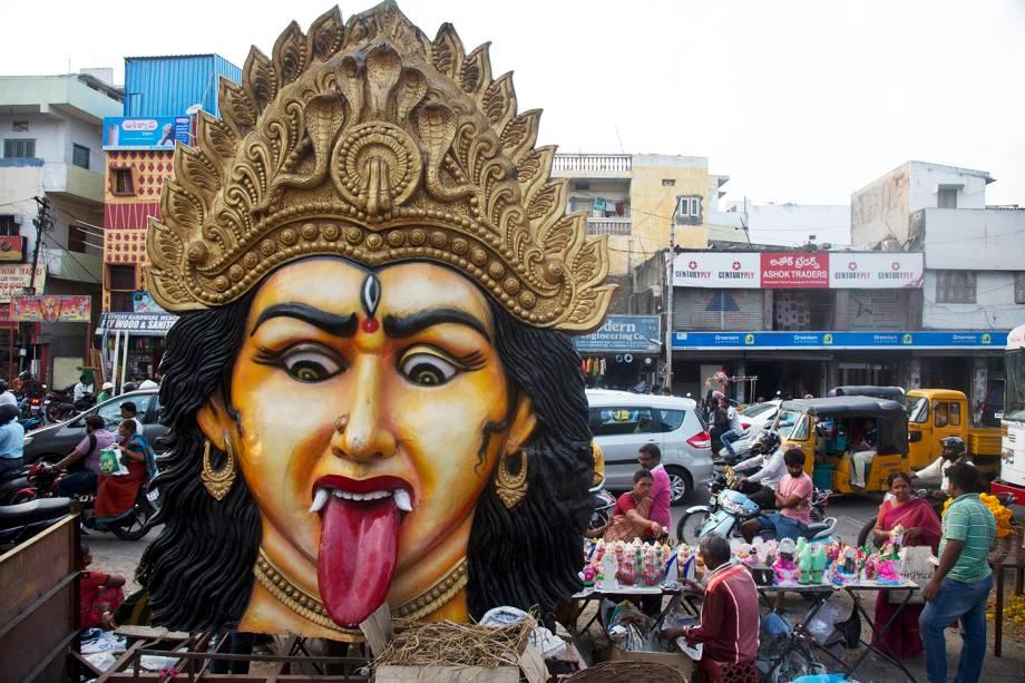 Devotos compram imagens da deusa Lakshmi , próximos de uma imagem gigante da deusa hindu Kali, utilizada para procissões religiosas, às vésperas do festival Diwali, na cidade indiana de Hyderabad - 06/11/2018