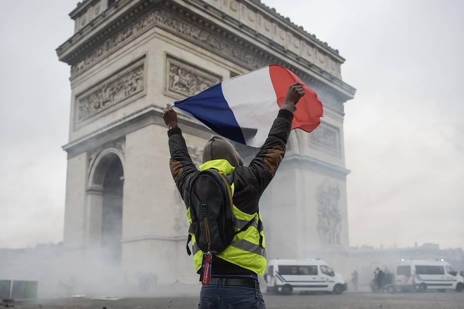 Manifestante segura uma bandeira francesa em meio a fumaça de gás lacrimogêneo lançado pela polícia em frente do Arco do Triunfo, na Champs Elysees, em Paris durante uma manifestação nacional contra o aumento dos preços do petróleo e do custo de vida - 24/11/2018