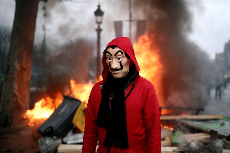 Manifestante caminha em frente a uma barricada durante protesto contra o aumento no preço dos combustíveis na Champs-Elysees, em Paris, França - 24/11/2018