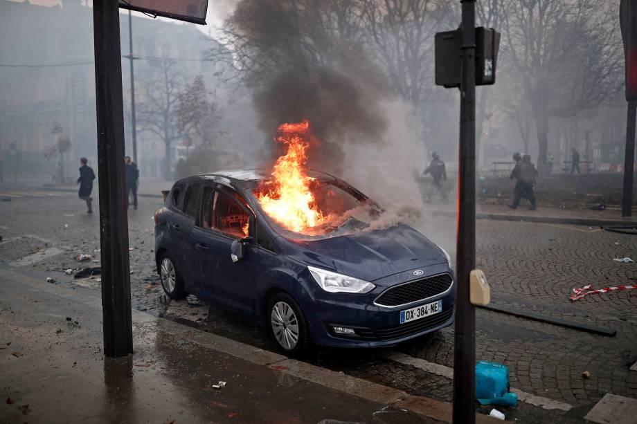 Carro é incendiado durante protesto contra o aumento do imposto sobre combustíveis na Champs Elysees, em Paris, França - 24/11/2018