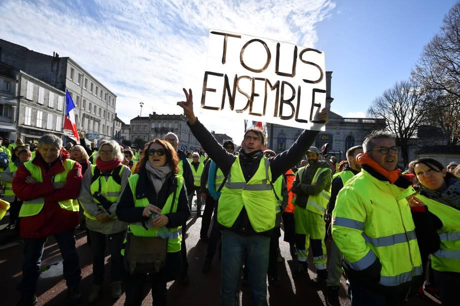 Manifestantes usando coletes amarelos (Gilets jaunes) gritam palavras de ordem e carregam e cartazes durante manifestação contra o aumento no preço dos combustíveis em Rochefort, no sudoeste da França - 24/11/2018