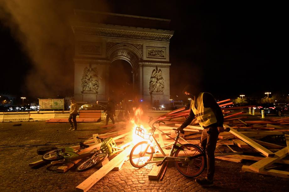 Manifestante coloca uma bicicleta em uma barricada em chamas durante protesto contra o aumento dos preços dos combustíveis e do custo de vida perto do Arco do Triunfo em Paris - 24/11/2018