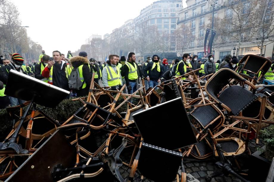 Manifestantes vestidos com coletes amarelos fazem barricadas com cadeiras na Champs Elysees, em Paris durante protesto nacional contra o aumento dos preços do petróleo e dos custos de vida - 24/11/2018