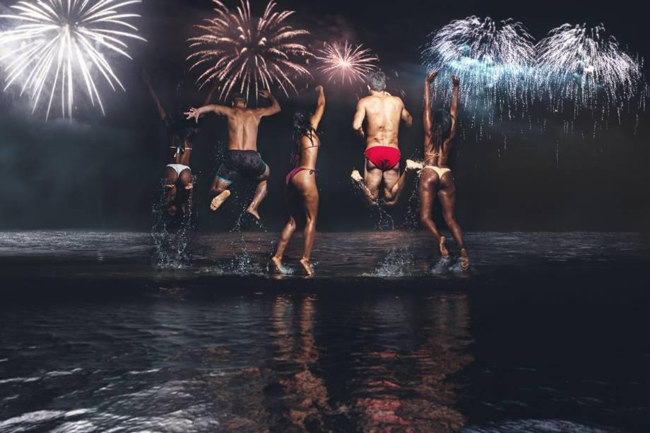 Grupo de amigos pulam ondas durante celebração de Ano Novo