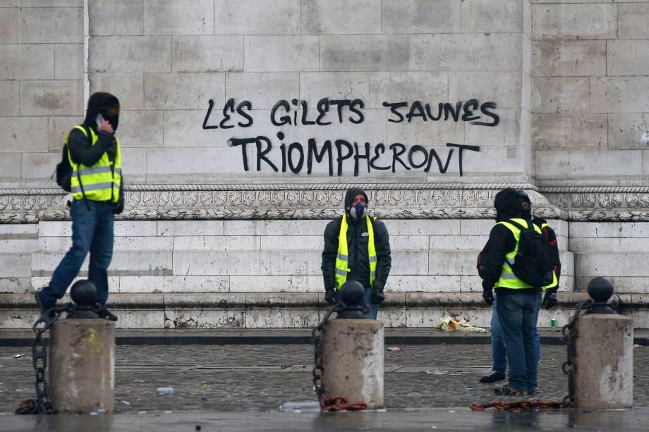 """Manifestantes escrevem """"jaquetas amarelas triunfarão"""" no Arco do Triunfo, em Paris, durante manifestação contra o aumento de impostos e o governo do presidente Macron - 01/12/2018"""