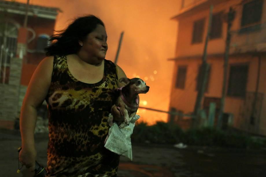 Mulher carrega seu cachorro após deixar sua casa durante incêndio de grandes proporções no bairro de Educandos, zona sul de Manaus - 17/12/2018