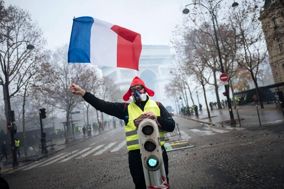 Um manifestante de colete amarelo e máscara de gás balança uma bandeira da França proximo ao Arco do Triunfo, em Paris, durante protesto - 01/12/2018