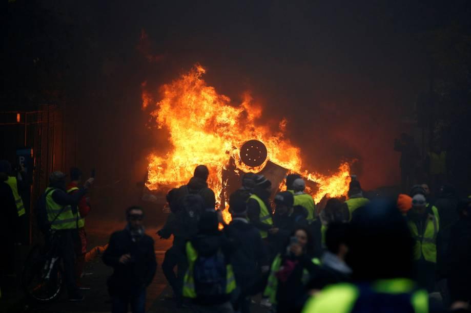 Manifestantes de colete amarelo são vistos próximos a um carro em chamas durante protesto na Place de l'Etoile em Paris, França - 01/12/2018