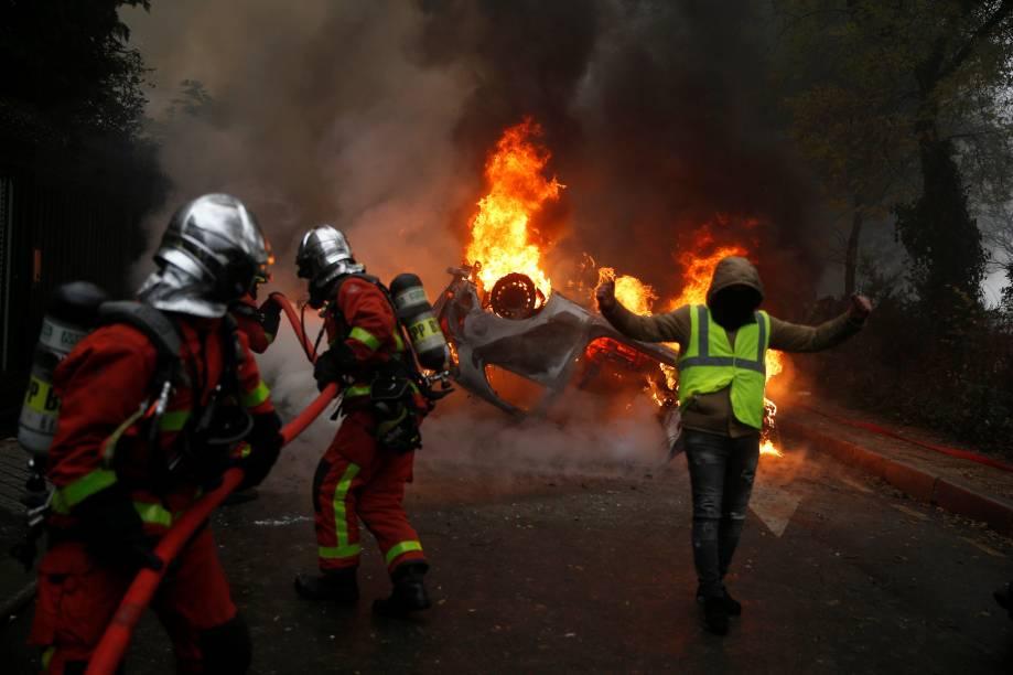 Manifestantes vestindo coletes amarelos, um símbolo de um protesto de motoristas franceses contra impostos mais elevados sobre o diesel, passa perto de um carro em chamas durante os protestos perto da Place de l'Etoile em Paris, França - 01/12/2018