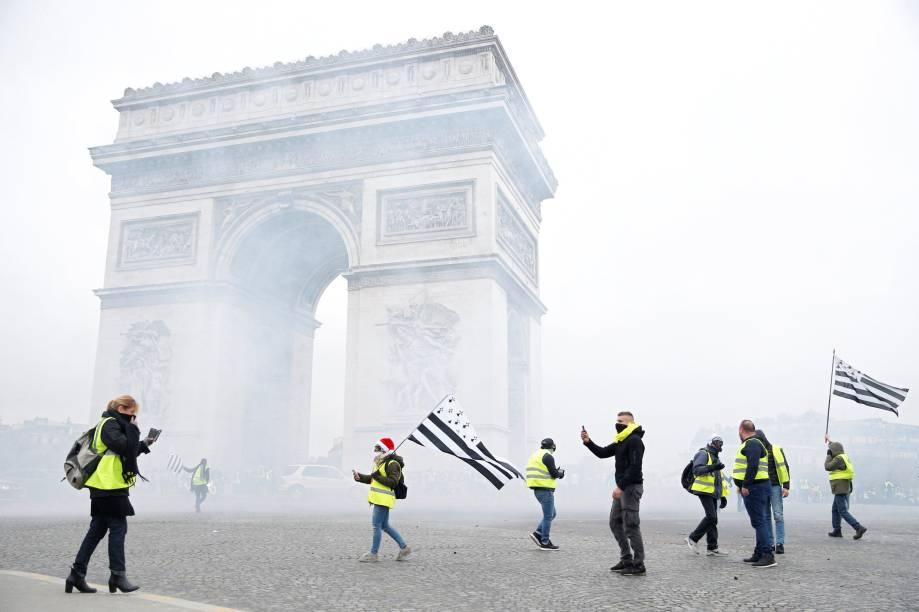 Uma nuvem de gás lacrimogêneo flutua proximo ao Arco do Triunfo, em Paris, enquanto manifestantes protestam contra a alta do preço dos combustíveis - 01/12/2018