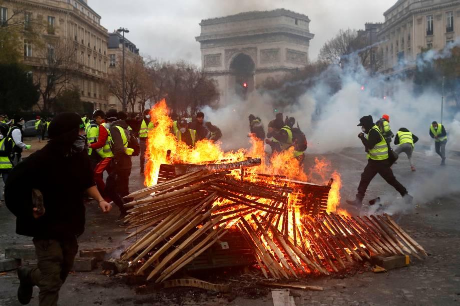 Manifestantes queimam madeiras durante um protesto contra o governo em Paris, na França - 01/12/2018