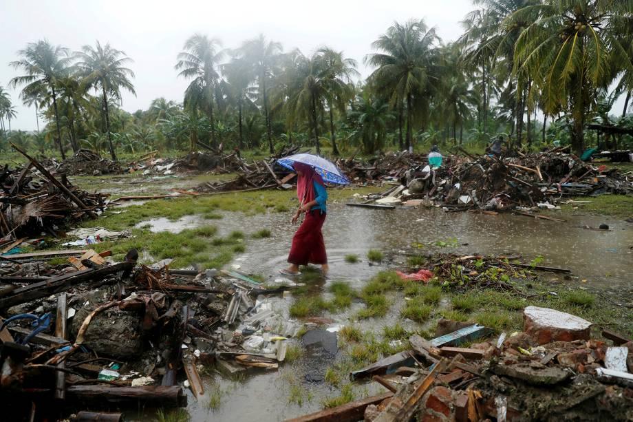 Mulher caminha pelos escombros causados pelo tsunami que atingiu a Indonésia, na cidade de Sumur - 26/12/2018