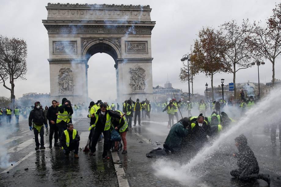 Manifestantes vestindo coletes amarelos, um símbolo de um protesto de motoristas franceses contra impostos mais altos no diesel, enfrentam a polícia de choque francesa durante os confrontos na Place de l'Etoile, perto do Arco do Triunfo, em Paris - 01/12/2018