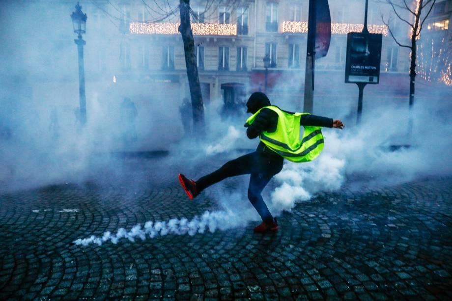 Manifestante com colete amarelo chuta artefato arremessado por policiais franceses durante protesto contra o governo em Paris  15/12/2018