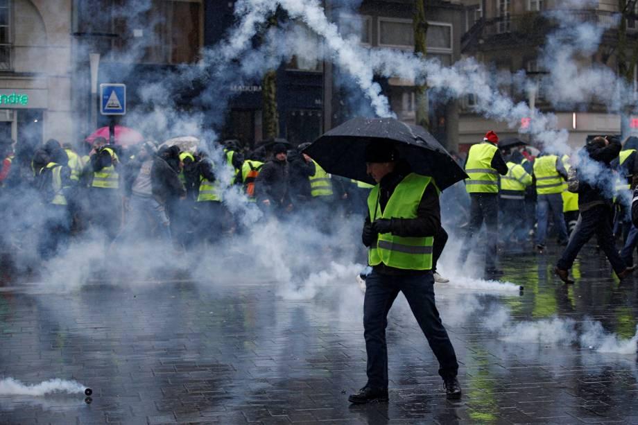 Bombas de gás lacrimogêneo são arremessadas contra manifestantes vestidos com coletes amarelos, durante protesto contra o governo realizado em Nantes, na França - 15/12/2018