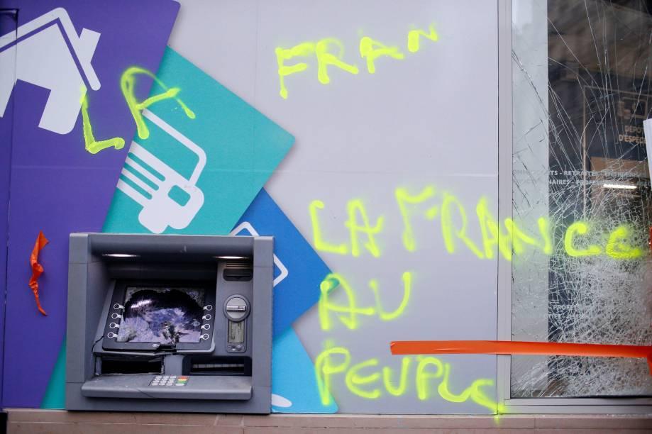 Uma pixação é vista ao lado de um caixa eletrônico depredado no dia seguinte das manifestações em Paris - 02/12/2017