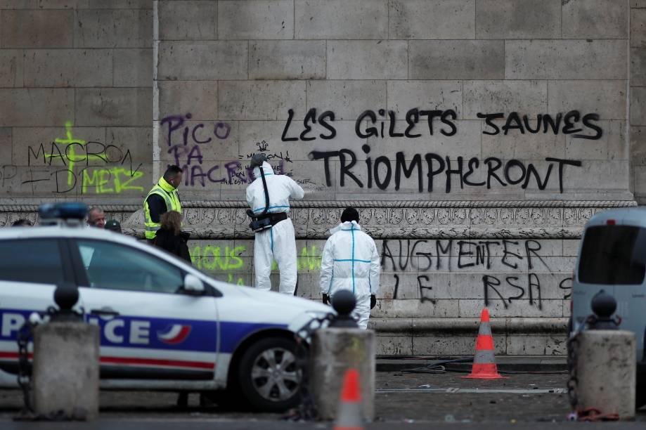 """Policiais trabalham em torno da mensagem feita no Arco do Triunfo """"Os coletes amarelos triunfarão"""", escrita durante as manifestações da última noite em Paris - 02/12/2018"""