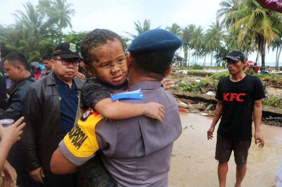 Garoto ferido é carregado por policial durante evacuação do hotel atingido por tsunami no distrito de Carita, localizado na província de Banten, na Indonésia - 23/12/2018