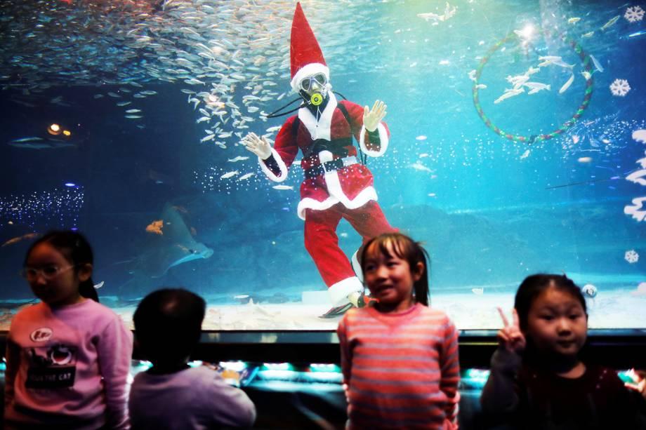 Mergulhador vestido de Papai Noel posa para foto com crianças durante evento promocional de Natal em Seul, na Coreia do Sul - 07/12/2018