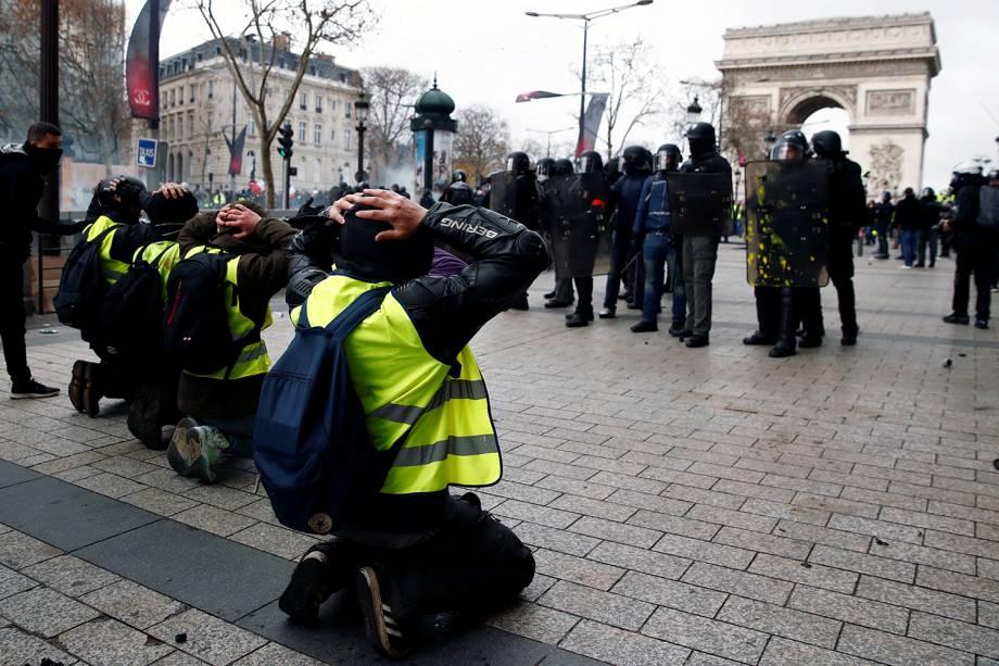 Manifestantes com coletes amarelos se ajoelham na Avenida Champs-Élysées próximo ao Arco do Triunfo e encara a Polícia francesa em Paris, França - 08/12/2018