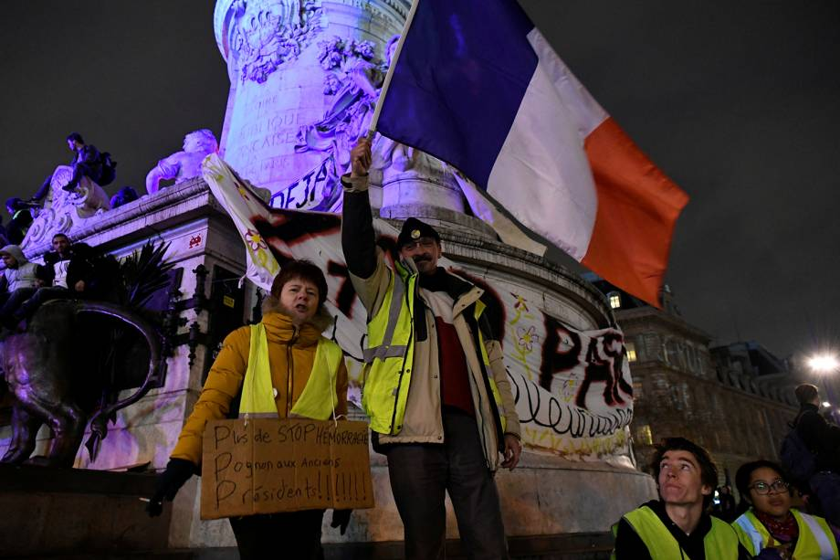 Manifestantes com coletes amarelos exibem cartazes e a bandeira da França durante protesto na Praça da República em Paris, França - 08/12/2018
