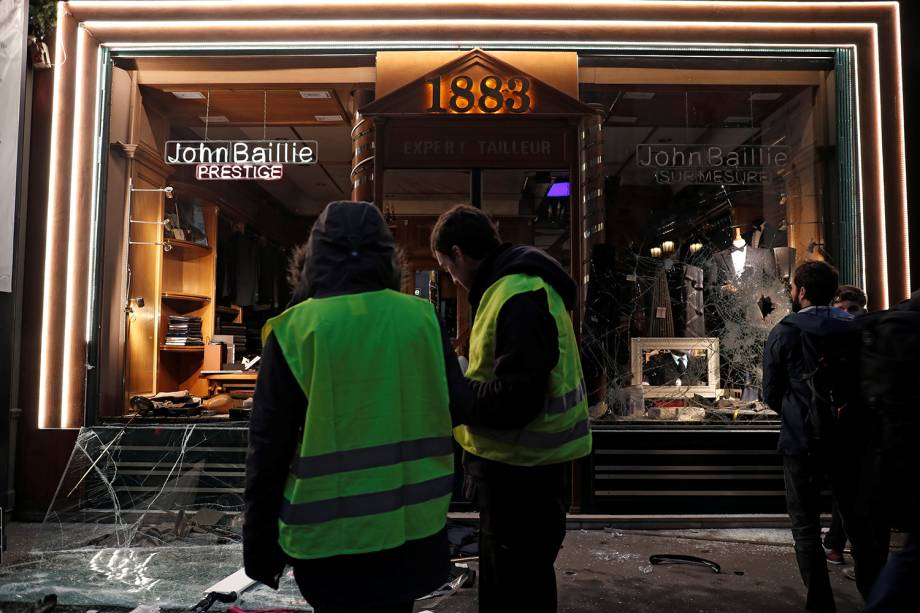 Manifestantes vestindo coletes amarelos param em frente a loja vandalizada durante manifestação em Paris, França - 08/12/2018