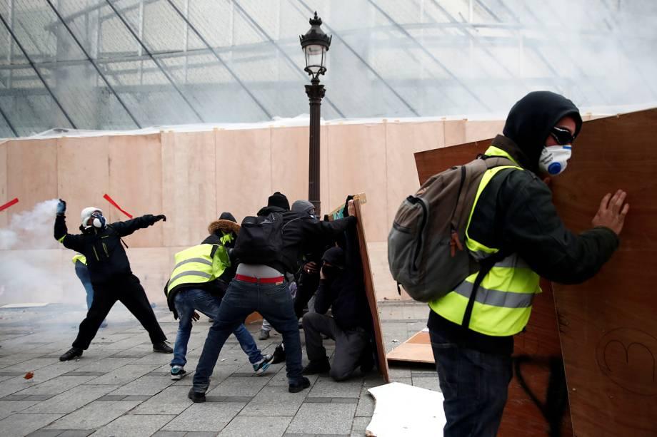 Manifestantes vestindo coletes amarelos entram em confronto com a Polícia na Avenida Champs-Élysées em Paris, França - 08/12/2018