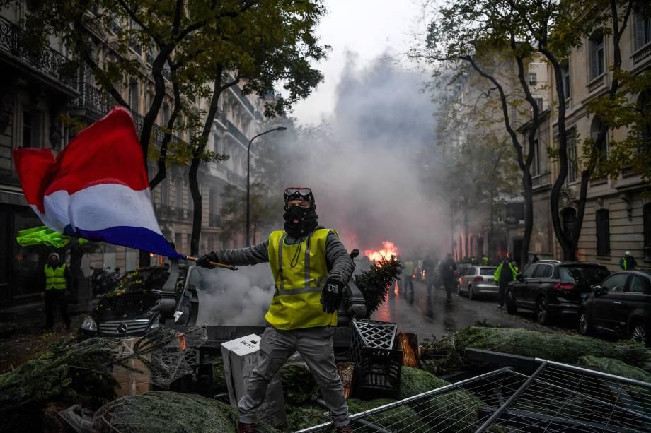 Manifestante usando um colete amarelo, símbolo dos protestos contra medidas econômicas do governo de Emmanuel Macron segura uma bandeira francesa durante ato em Paris - 01/12/2018