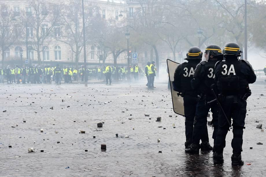 Oficiais da polícia de choque permanecem em posição durante confrontos com manifestantes na  Champs-Elysées em Paris - 01/12/2018