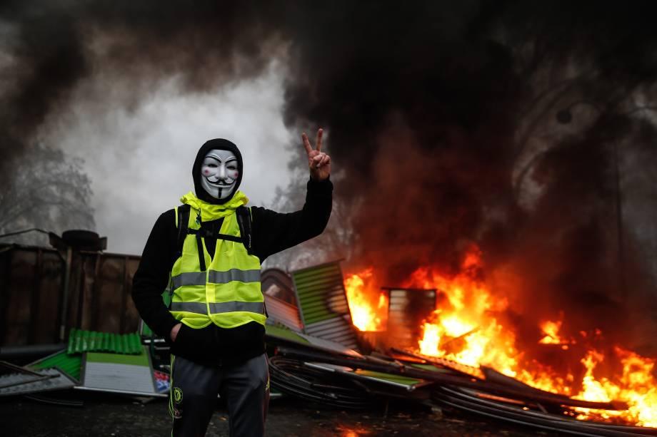Manifestante usa uma máscara de Guy Fawkes perto de uma barricada em chamas durante protesto dos coletes amarelos (Gilets jaunes) contra o aumento dos preços do diesel e do custo de vida em Paris - 01/12/2018