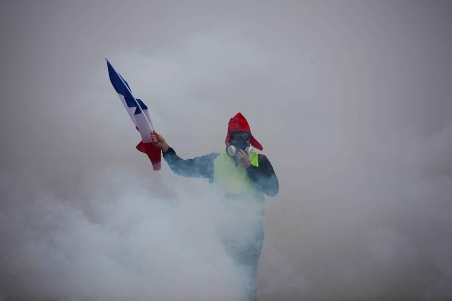 Manifestante segura uma bandeira francesa em meio à fumaça de gás lacrimogêneo durante protesto contra o aumento dos preços do diesel e do custo de vida em Paris - 01/12/2018