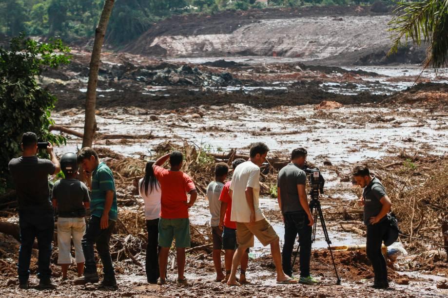 Pessoas observam o mar de lama após o rompimento de uma barragem na mina de ferro do Feijão, em Brumadinho (MG) - 25/01/2019