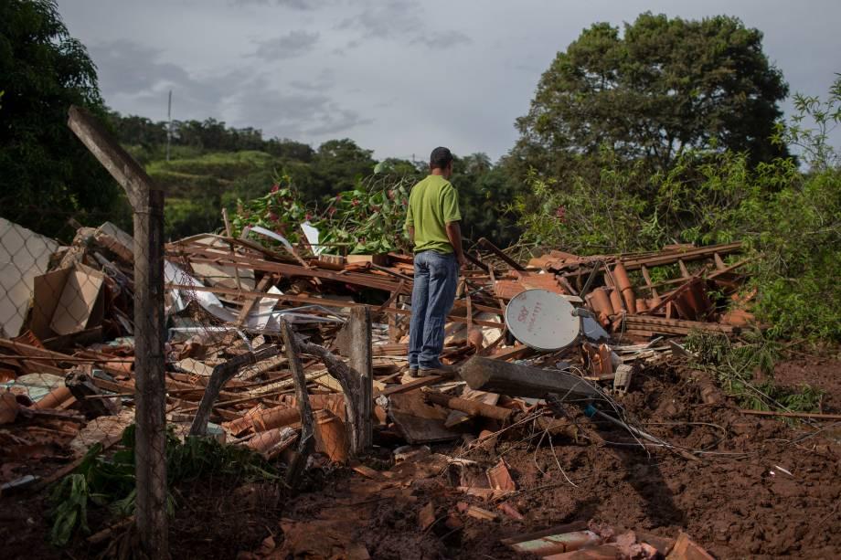 Homem caminha sobre os escombros de uma casa na comunidade do Parque da Cachoeira, um dia após o colapso de uma barragem pertencente à mineradora Vale perto da cidade de Brumadinho (MG) - 26/2019