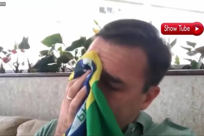 Flavio Bolsonaro enxuga as lágrimas com uma bandeira do Brasil ao falar do pai
