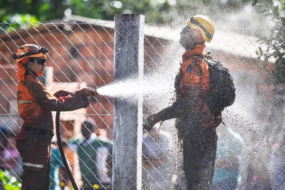 Membros de equipes de resgate se lavam após operação de busca por vítimas do rompimento de barragem em Brumadinho (MG) - 27/01/2019